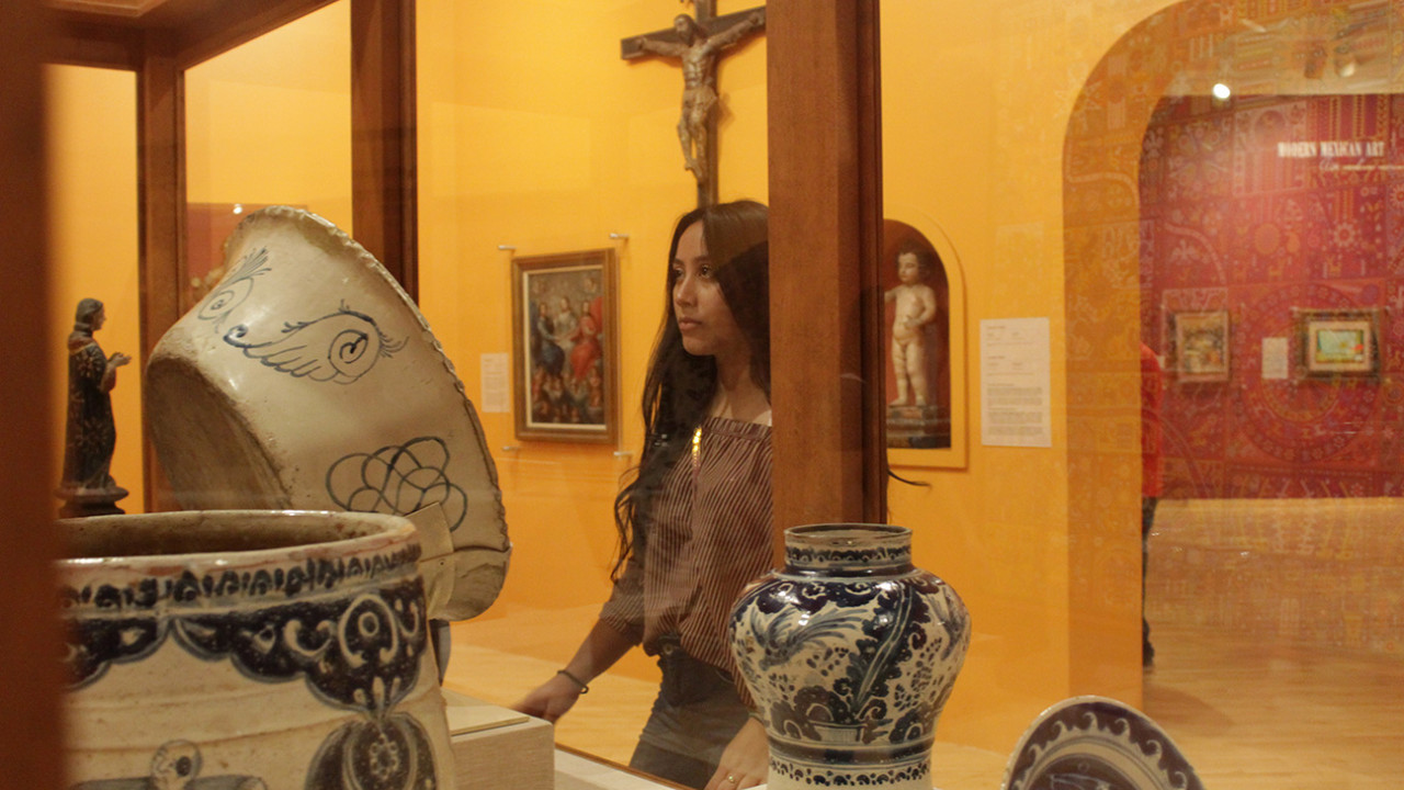 Student standing and looking into glass case with Mexican artifacts.