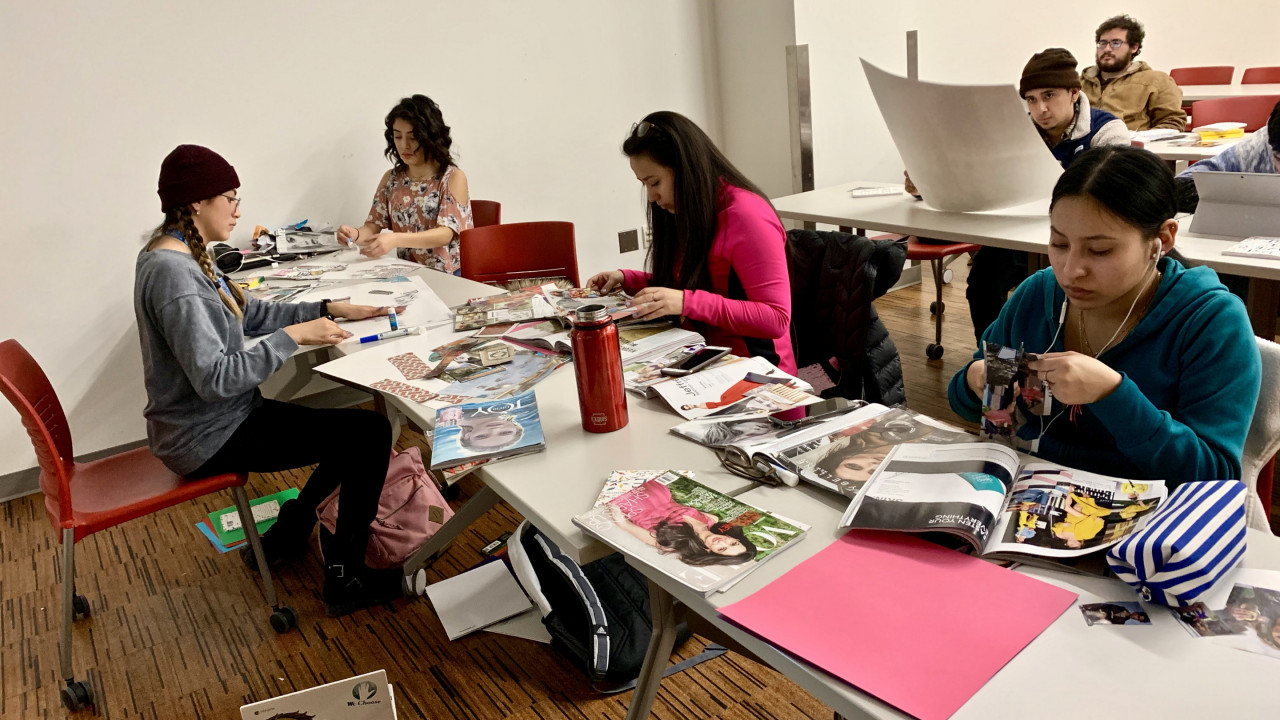 Students sitting at a long table cutting out images from magazines.