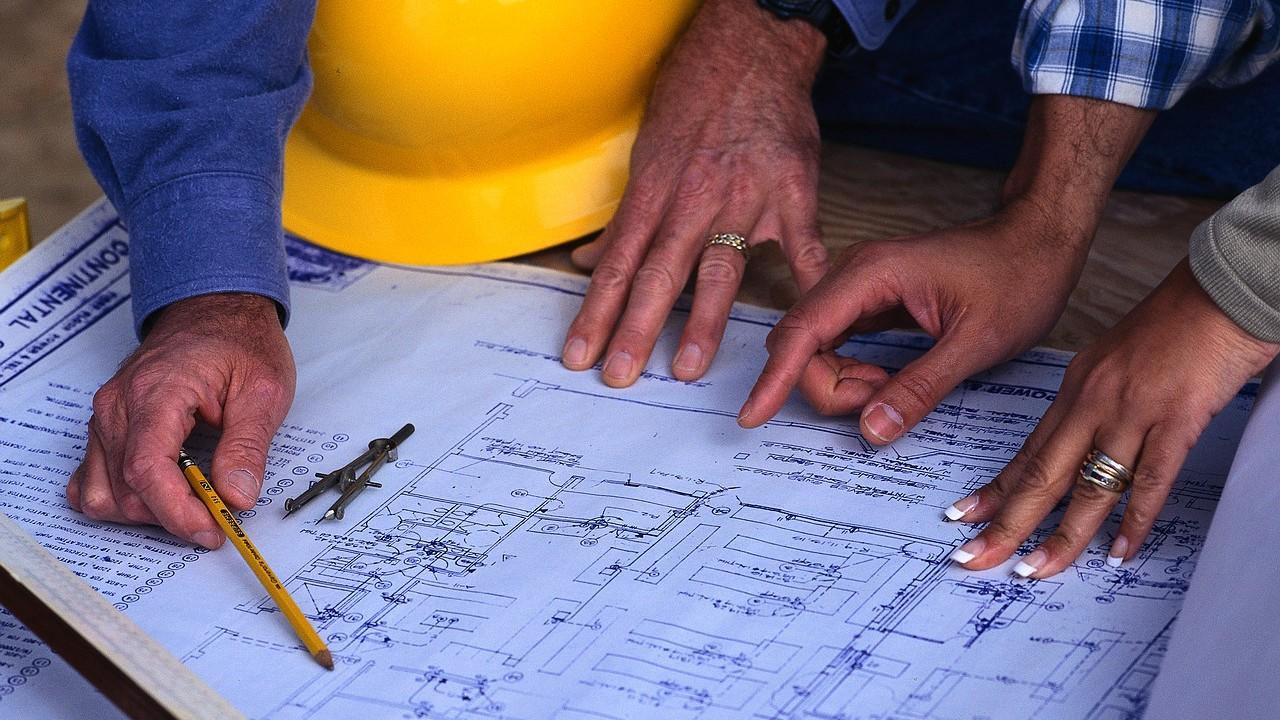Engineers look at blueprints.