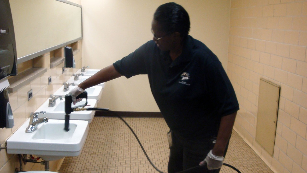 A custodial employee cleaning a bathroom on campus