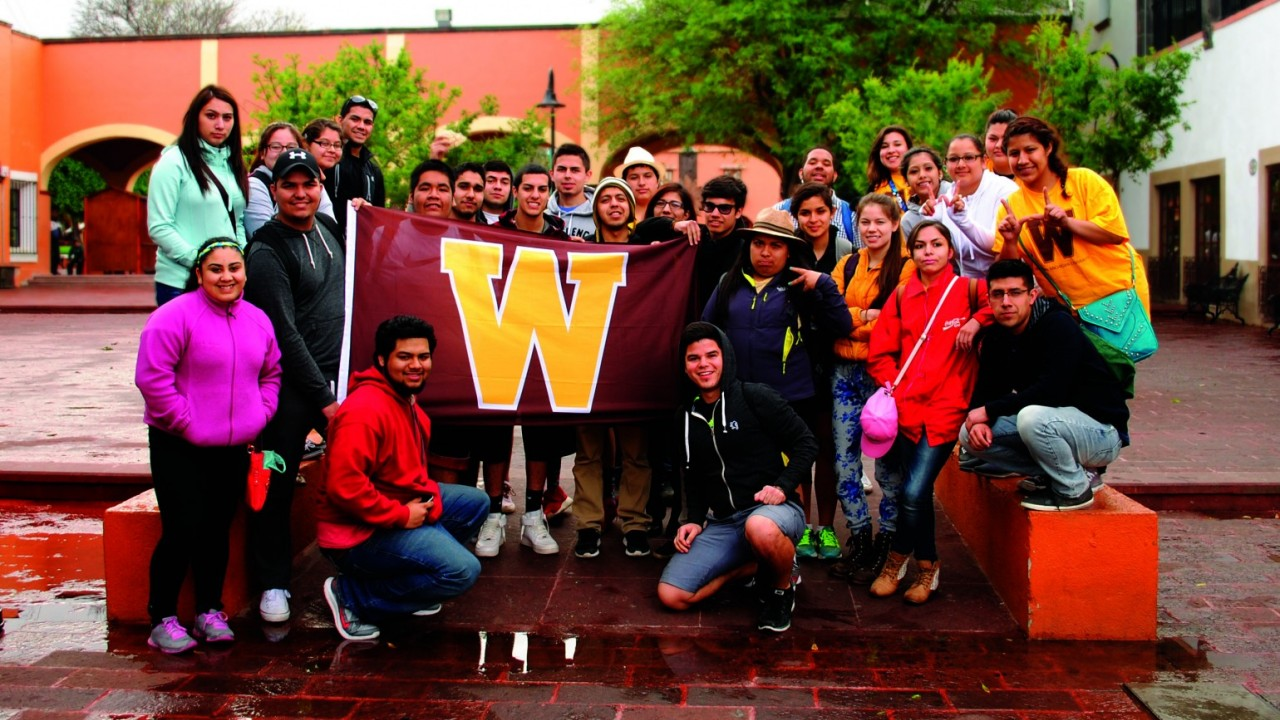 Group of students facing the camera holding a flag with the W logo