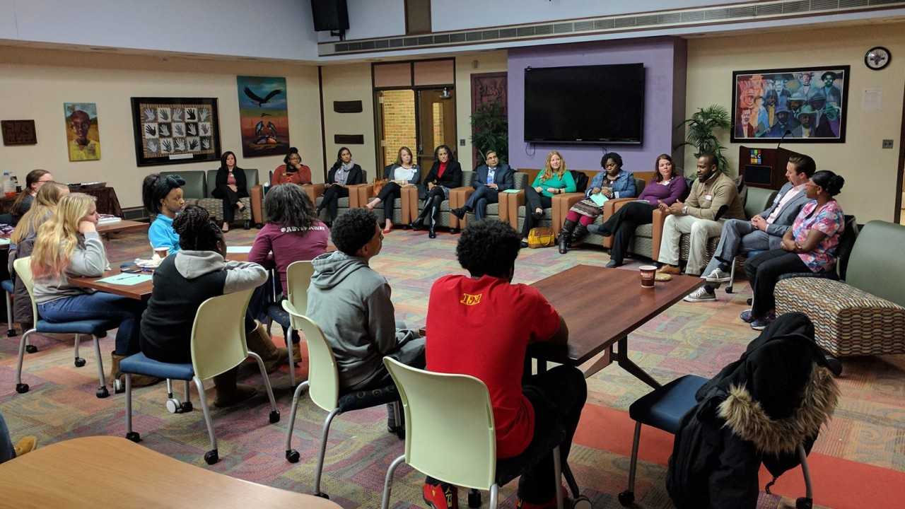 Students and professional staff from the community sitting in a discussion circle in the multicultural center