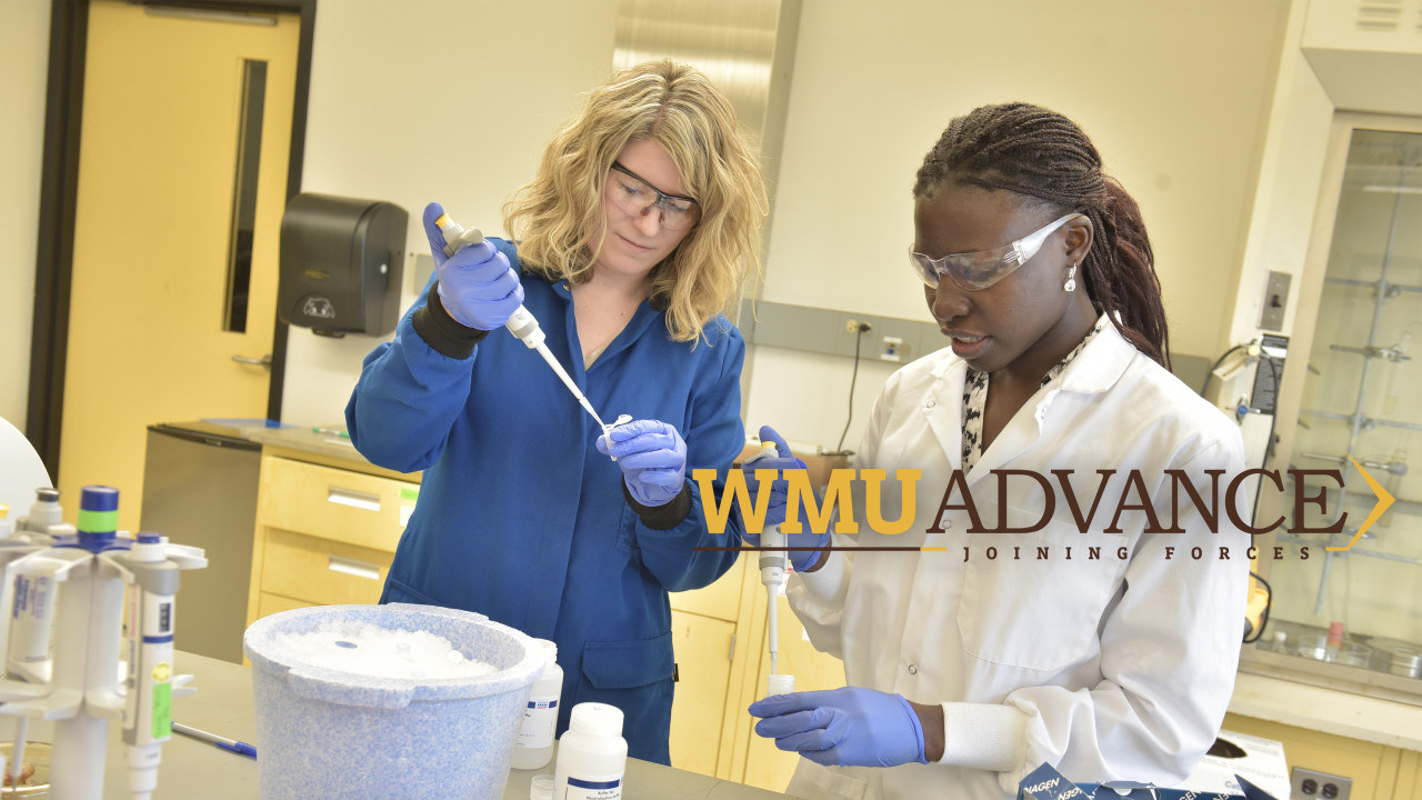 A female professor and student squeezing tubes in a science lab.