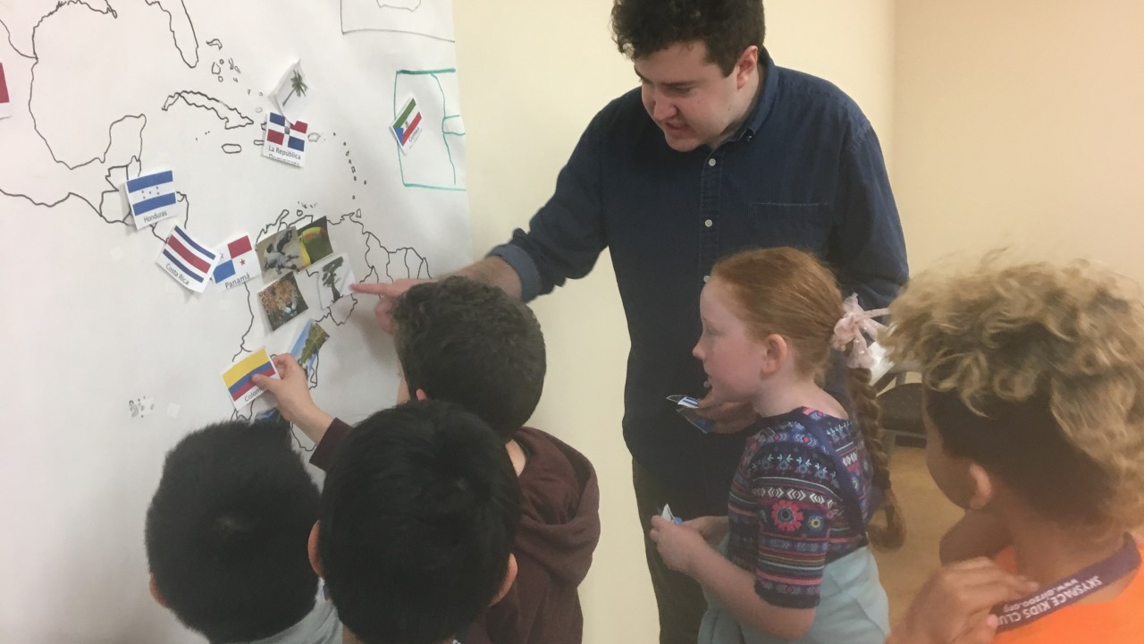 Mitch Barrett points to a map on the wall helping third graders identify countries on the map