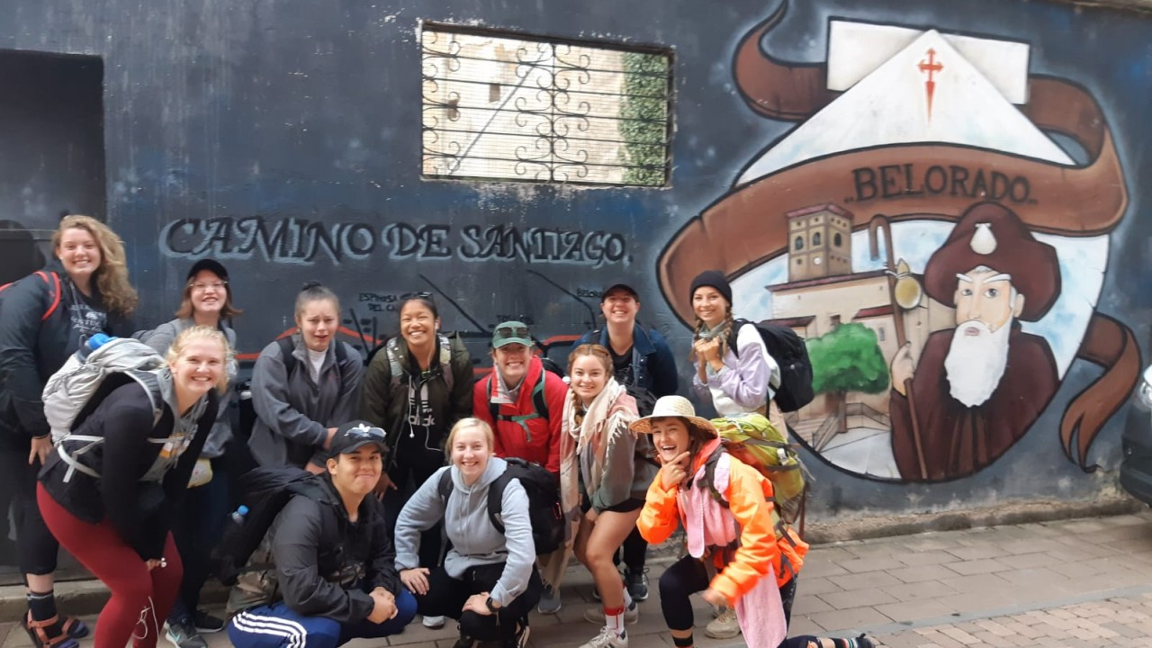 Students gathered outside in front of a mural of Camino de Santiago