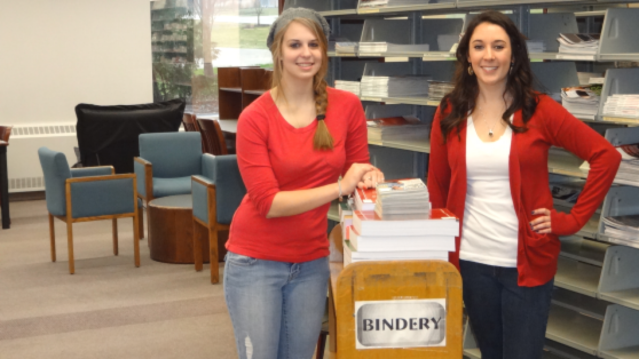 Two student assistants in the bindery area posing with books on a cart.