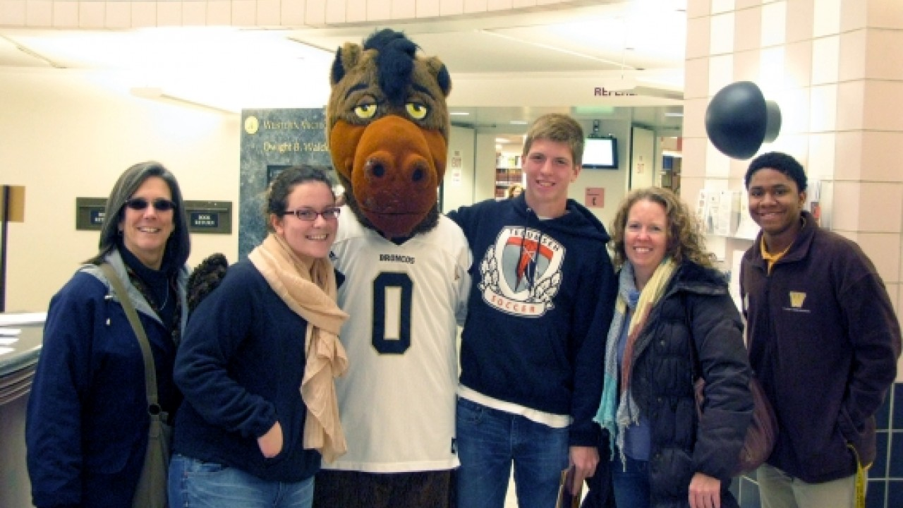 A group of students and parents posing with Buster Bronco in Waldo Library.