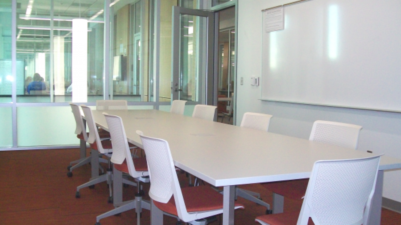 An empty Education Library Group Study Room with long table and whiteboard.