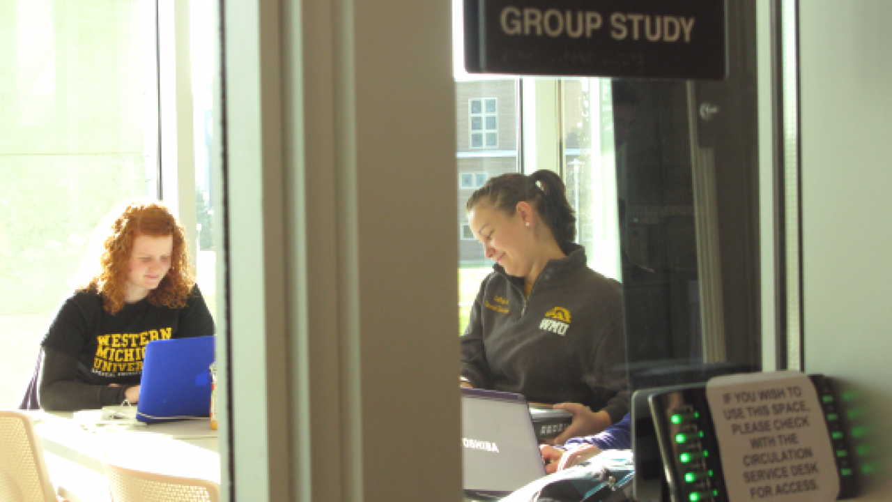 Two female students collaborating in a group study room.