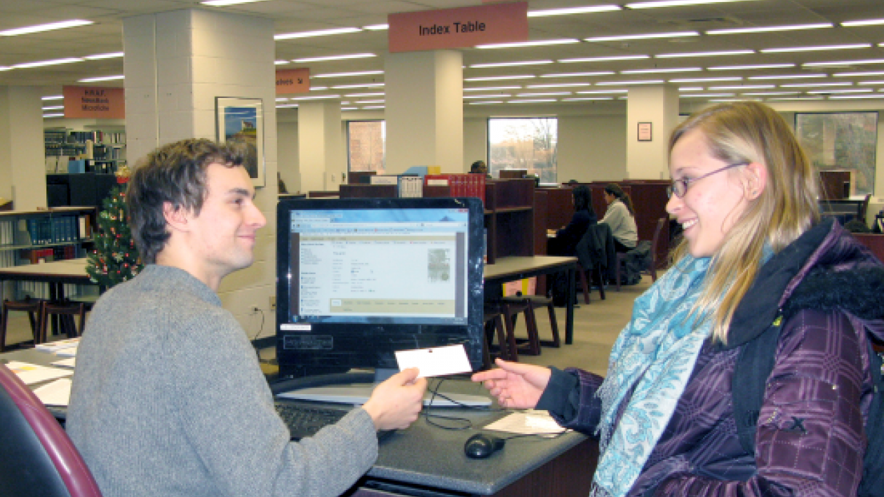 Student employee at Central Reference assisting a patron