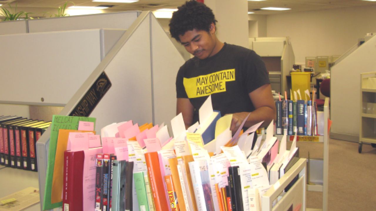 Student employee processing interlibrary loan books and other materials.