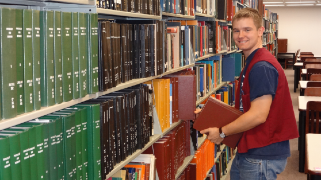 A student employee shelving books in Waldo Library.