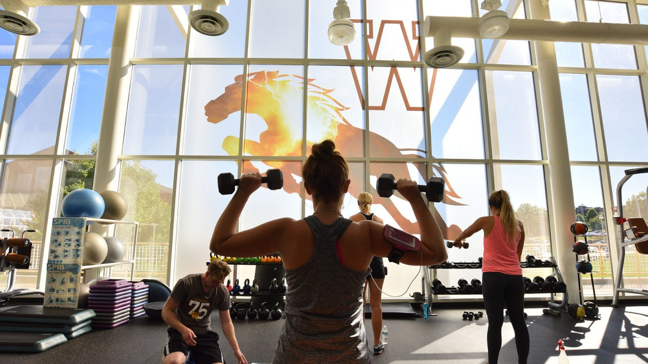 Weight room photo of a female using dumb bells in front of the thunder bronco window