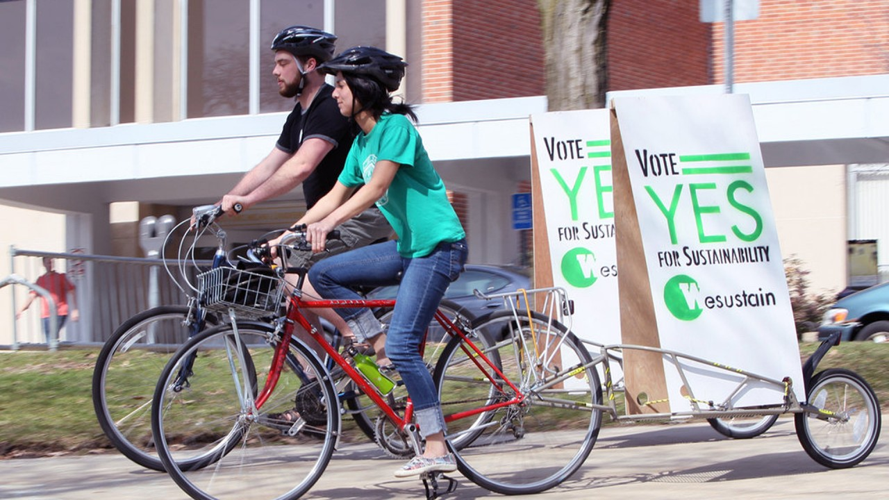 Chris Caprara and Kaitlyn Shields pull bicycle billboards.