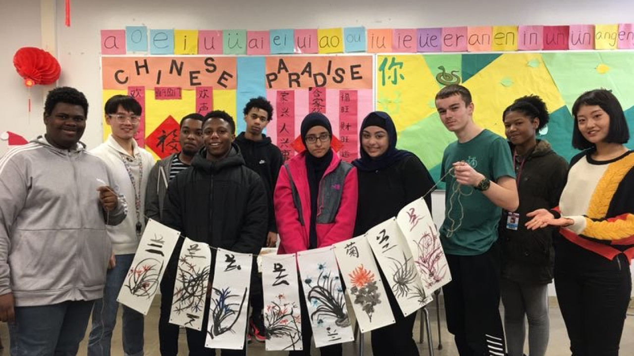 Kalamazoo Central High School students display their Chinese painting with the teachers