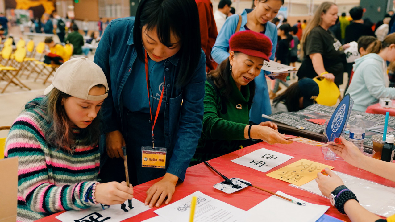 Participants practice calligraphy at China Festival