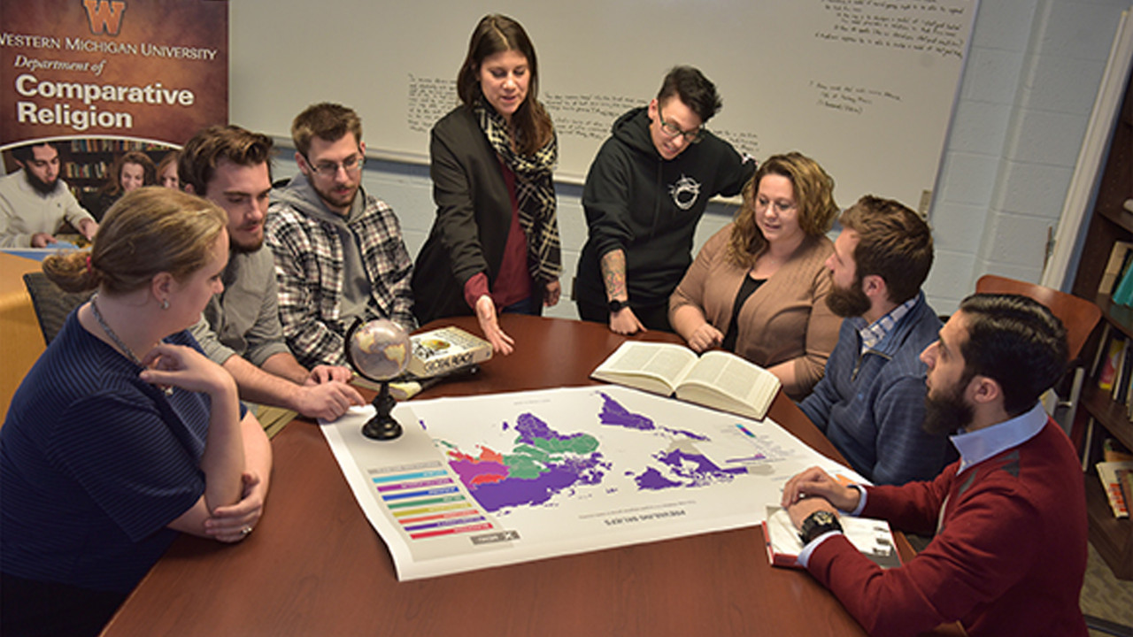 Seven students at table with faculty member looking over world map of religious regions