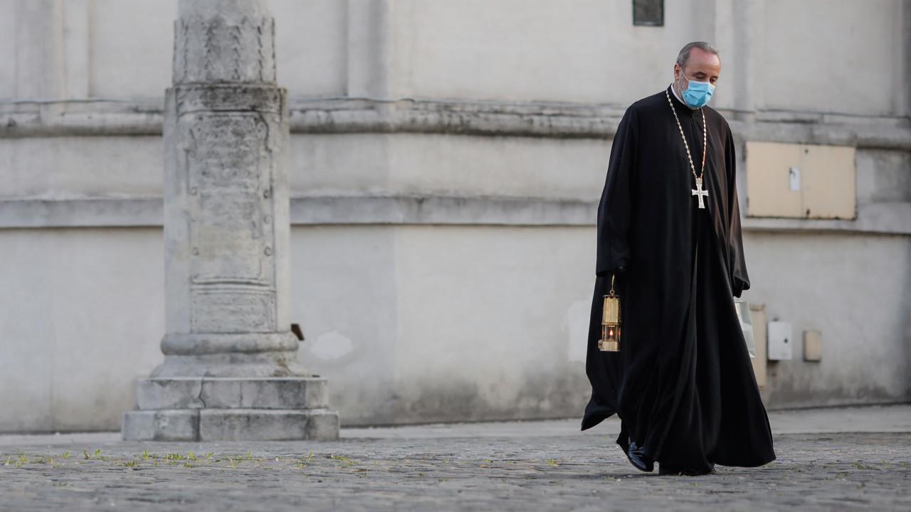 Priest wearing a mask, walking outside near a church