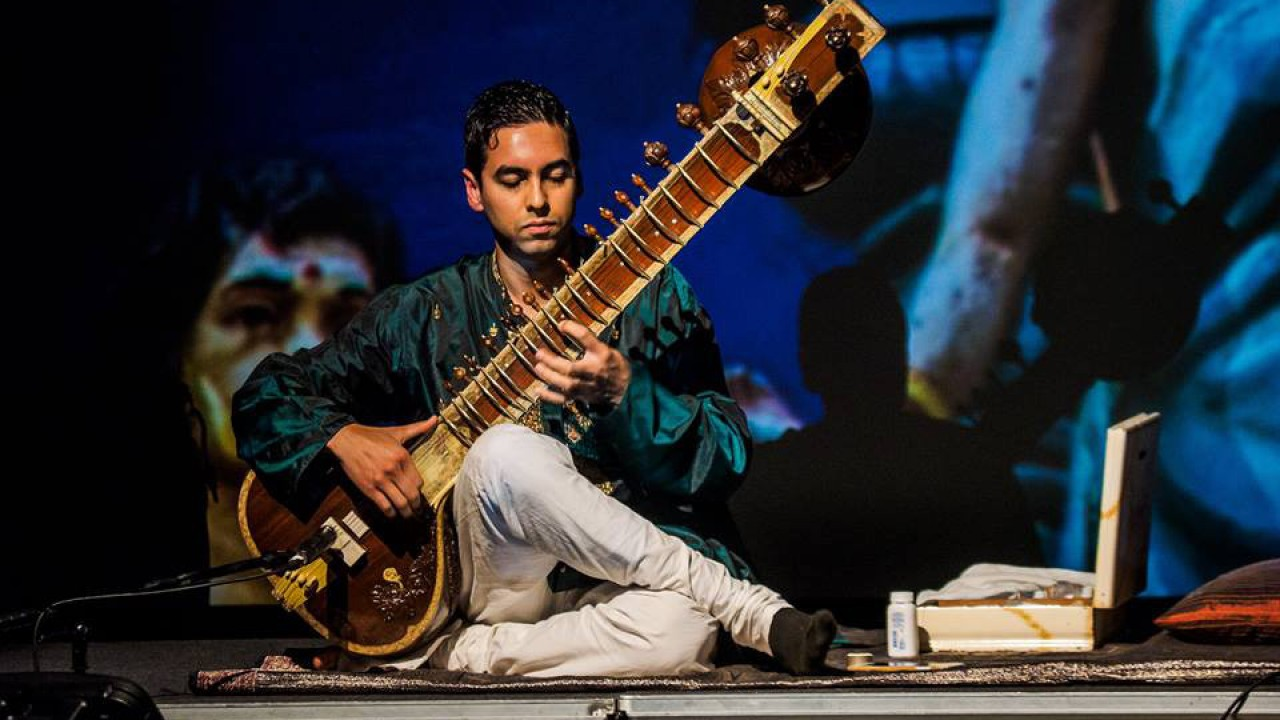 sitarist Arjun Verma sitting on stage wearing a teal shirt