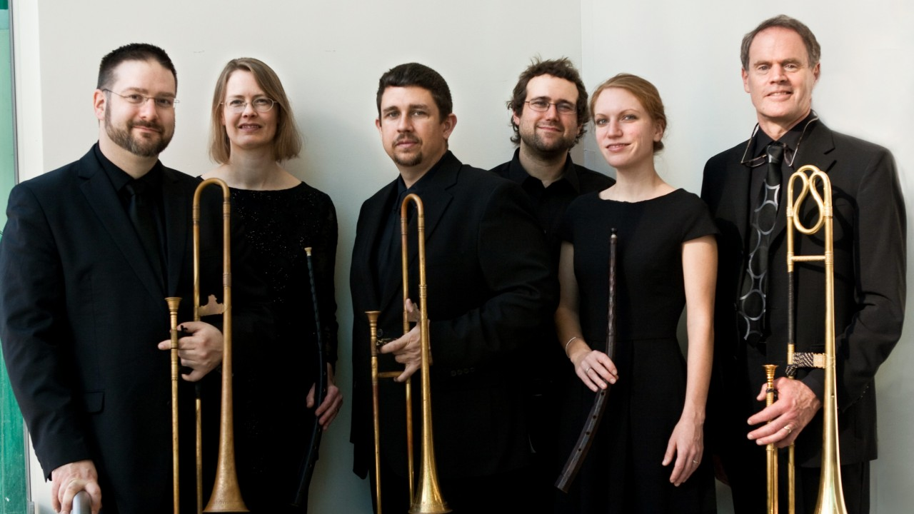 dark horse consort holding brass instruments against a cream and teal background. The group has 4 men and 2 women all wearing black.
