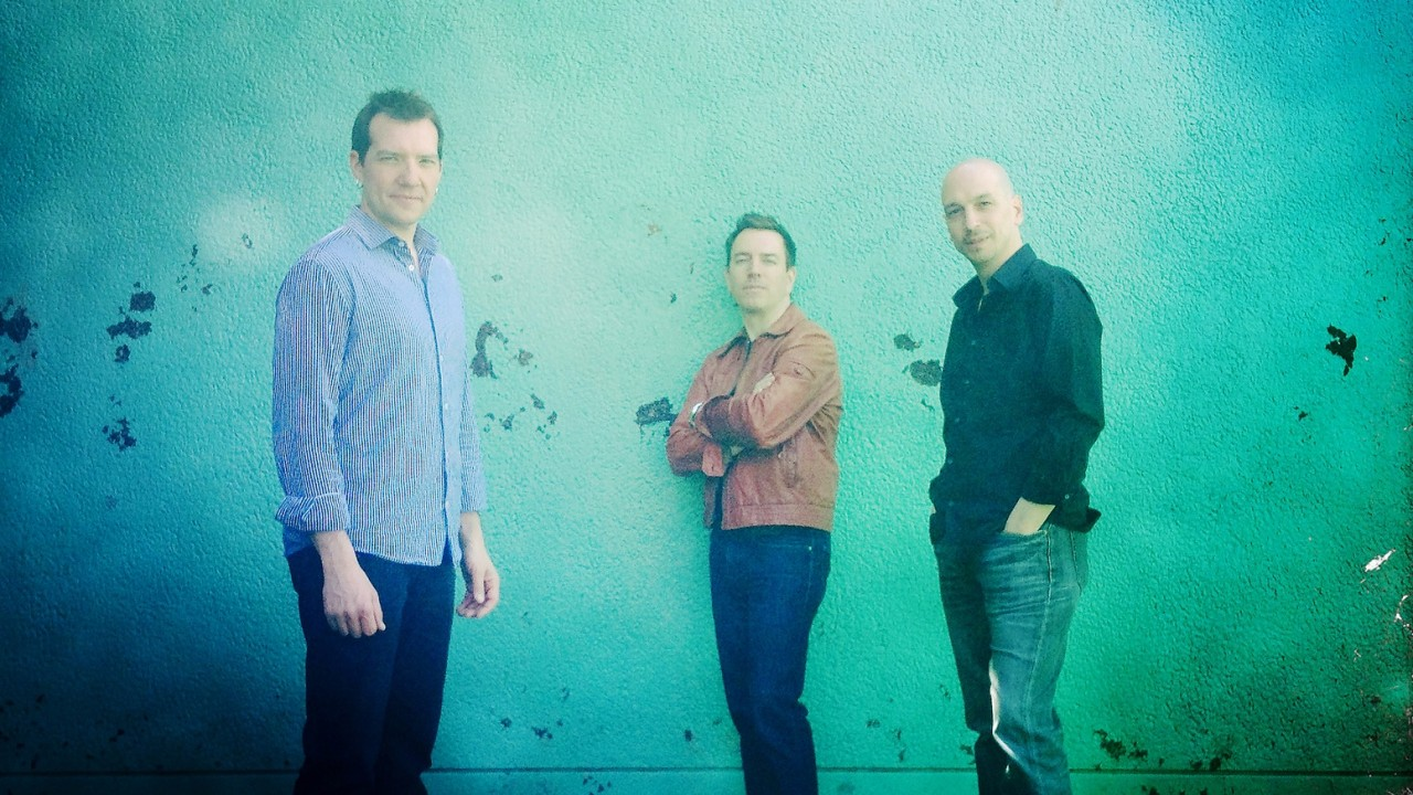 image of three musicians in long sleeve shirts and jeans standing against a teal wall