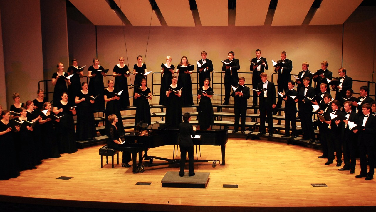 a choir performing on stage dressed all in black with a piano in the center of their arch