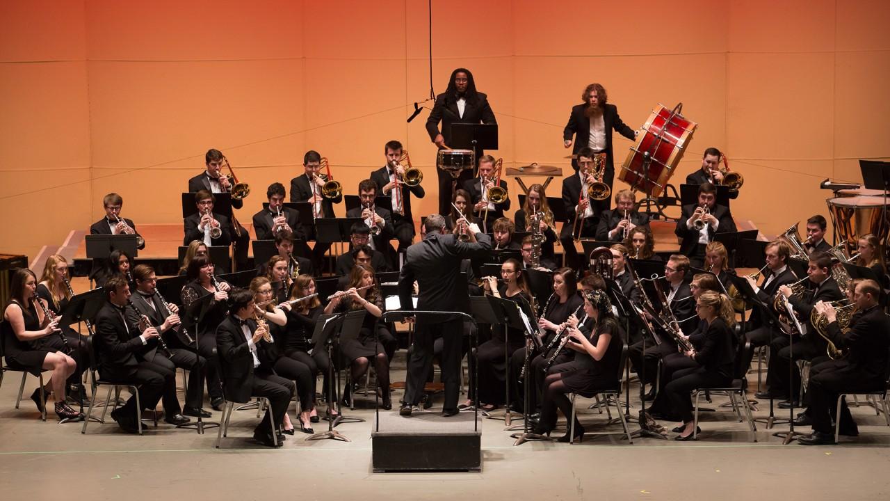 the university symphonic band on stage at miller auditorium under orange light.