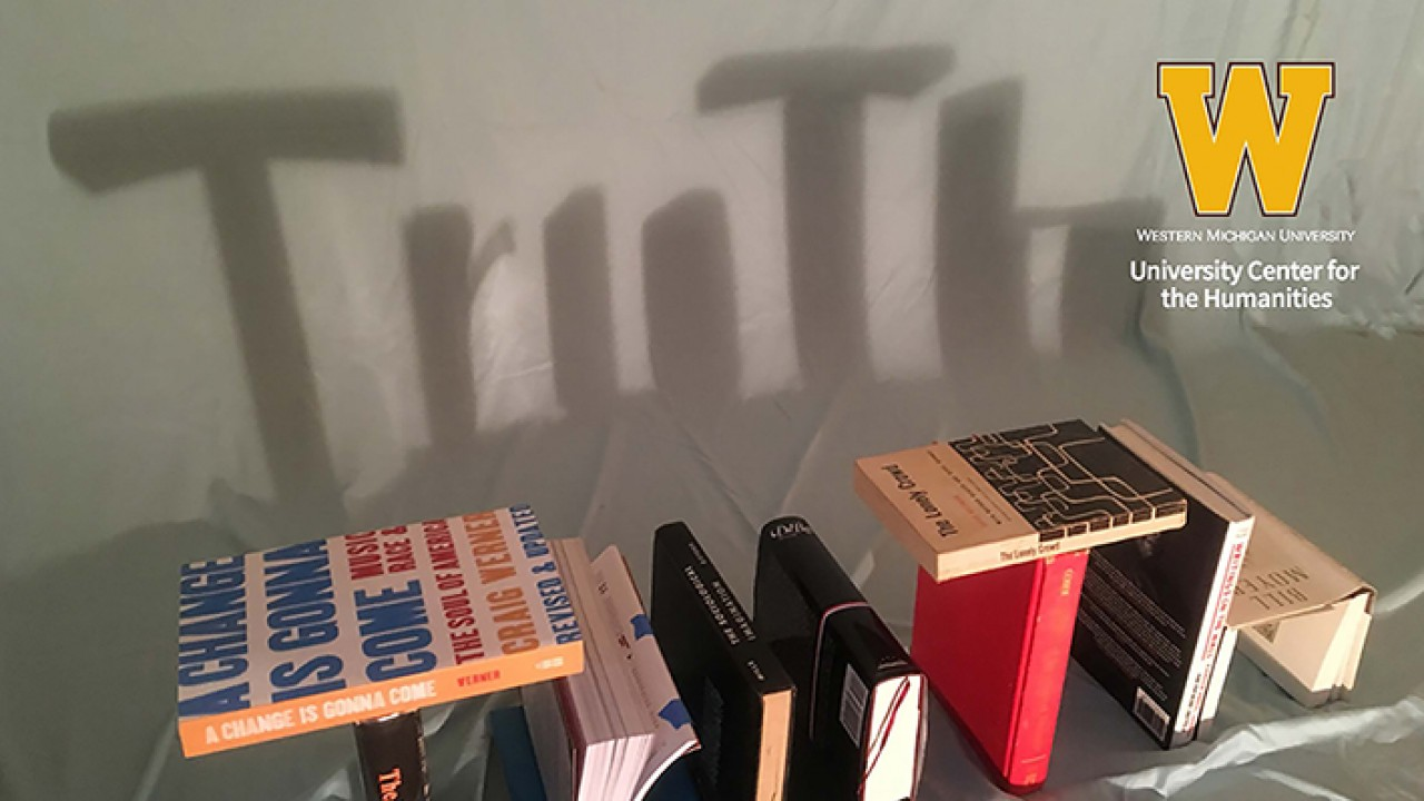 "Stack of books that spell out the word ""truth,"" with a shadow of the word on the wall behind the books"