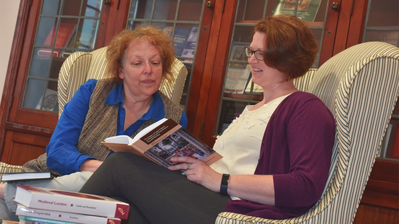 Image of Jana Schulman and Theresa Whitaker perusing books published by Medieval Institute Publications.