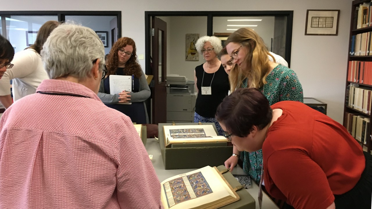 Image of students consulting rare books in Special Collections.
