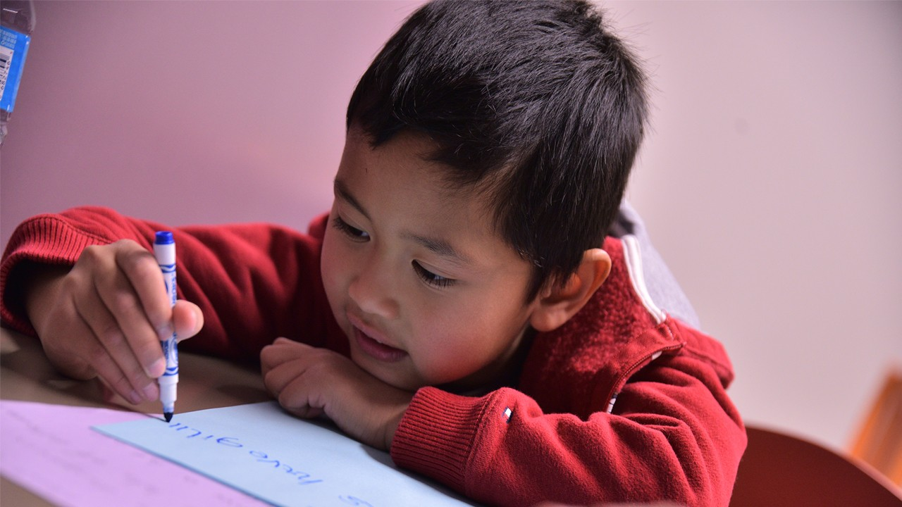 child drawing on a piece of paper