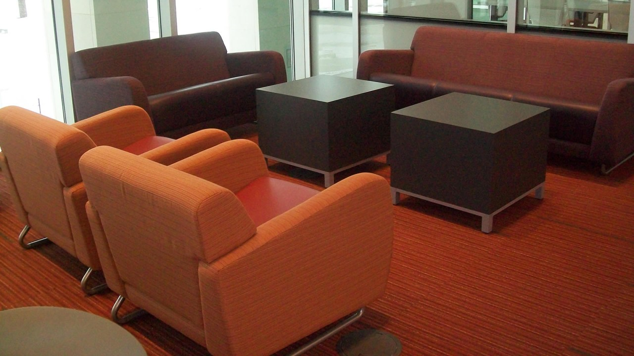 Seating area with two couches, two chairs and two wooden tables at Swain Education Library in Sangren Hall.