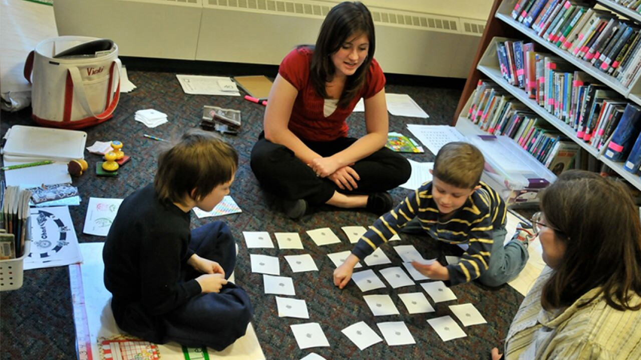 teacher working with students playing a memory game