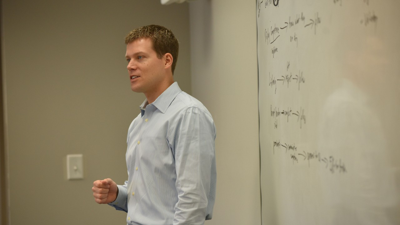 Photo of male faculty member talking in front of a white board