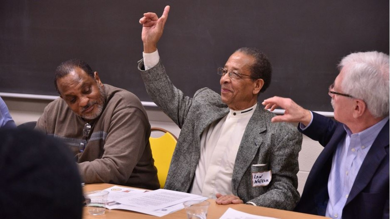 dr. walker raising his hand in a group discussion