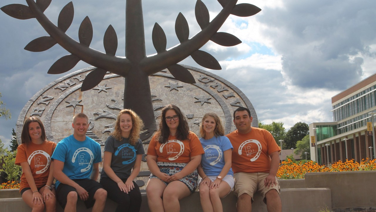 Students sitting in front of tree sculpture