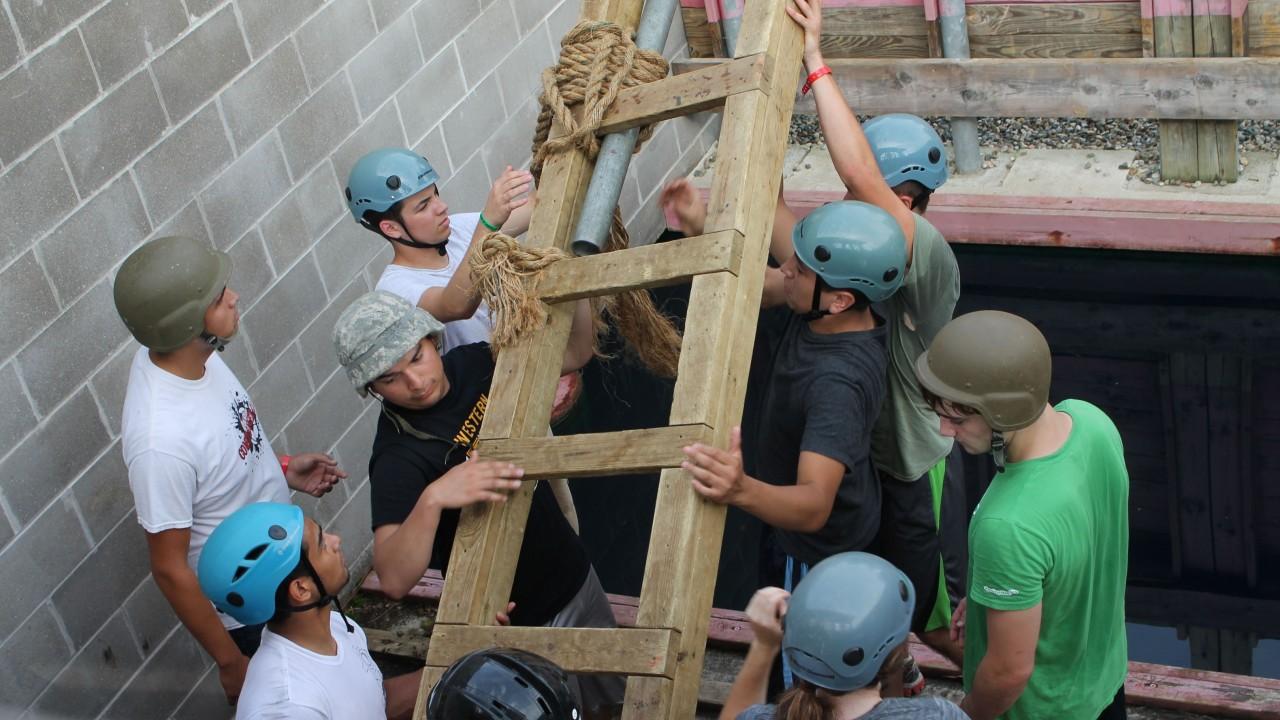 Students hoisting a ladder