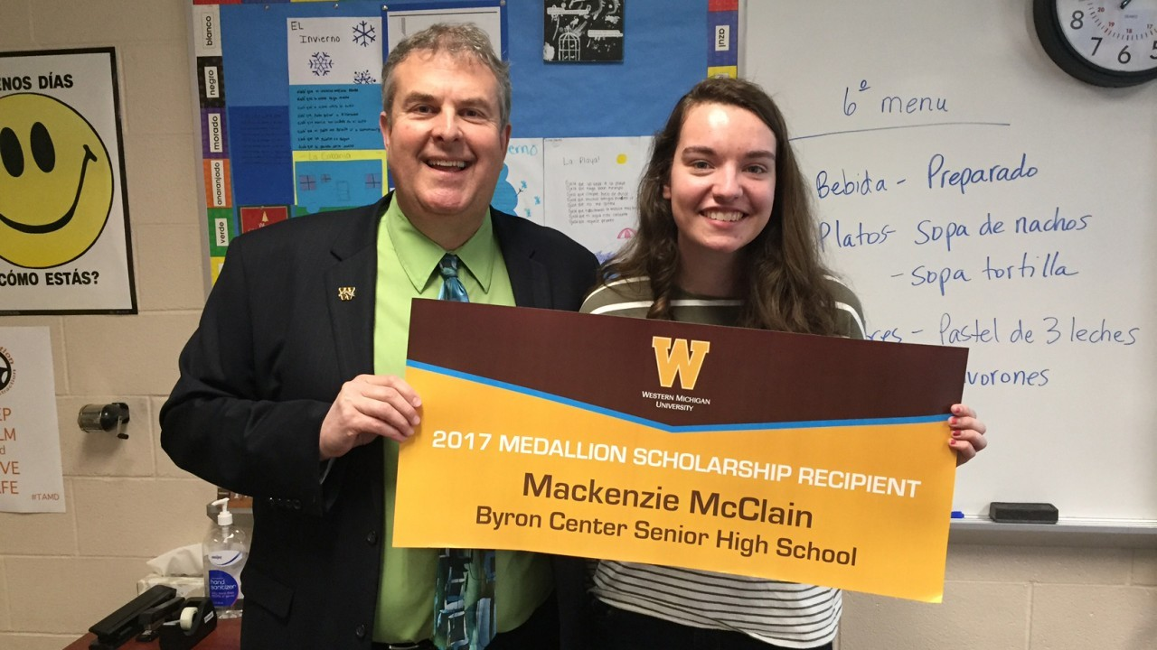 student and professor holding a sign that says 2017 medallion scholarship recipient mackenzie mcclain byron center senior high school