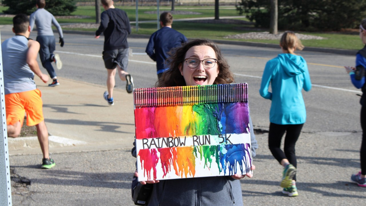 A photo of a student holding a Rainbow Run sign
