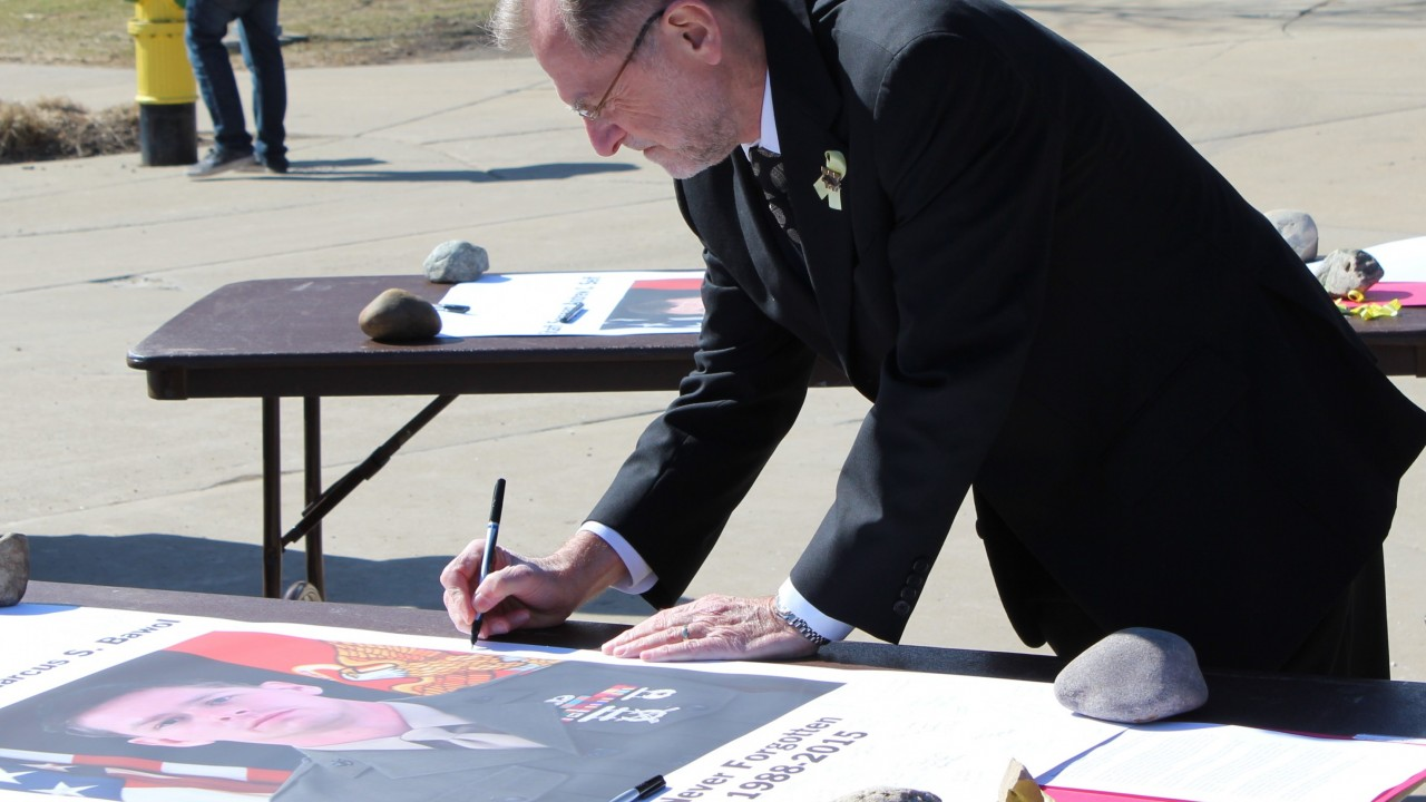 President Dunn signing a document to honor fallen Michigan marines