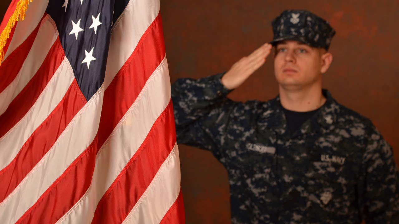 A student veteran saluting the American flag