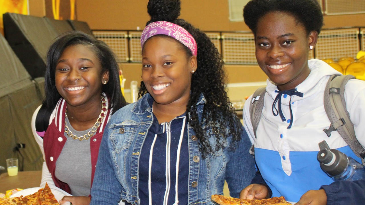Students smiling and eating pizza during an Alpha event