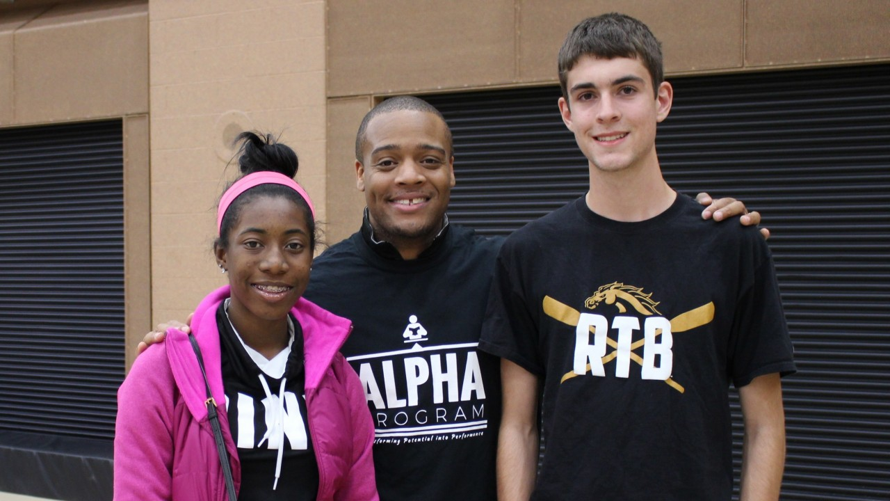 Director Walter Malone posing for a photo with two scholarship winners. All three people are smiling.