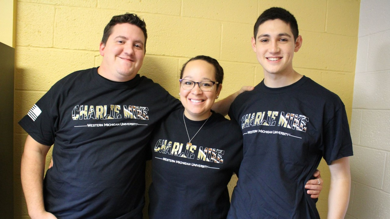"Three smiling students wearing Charlie Mike t-shirts, WMU's first Universitywide ""unit"" t-shirt for military students"
