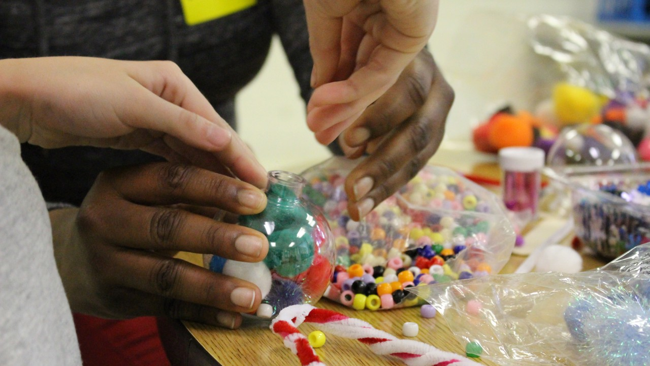 A WMU student working with an elementary student to create a holiday ornament. The WMU student's hands are holding the ornament while the elementary student's hands are inserting beads and cotton balls.