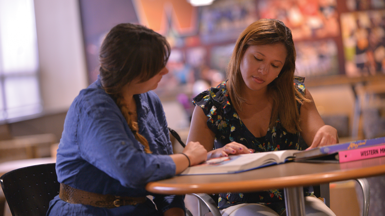 A student mentor helping a student with an assignment. The mentor is listening as the student reads from a textbook.
