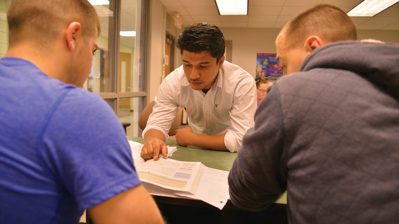 A student mentor assisting two students with an assignment. The mentor is pointing to information in a textbook while the other students are watching and taking notes.
