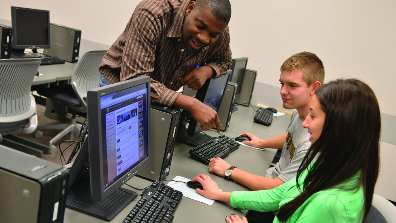 Two students working on computers while an instructor smiles and offers help
