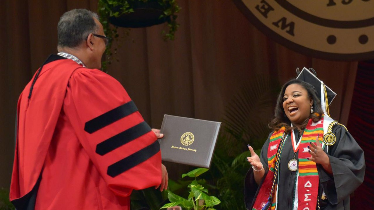 A smiling student preparing to shake Dr. Montgomery's hand and receive a diploma during commencement