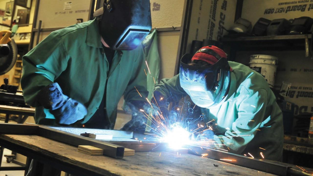Two people welding